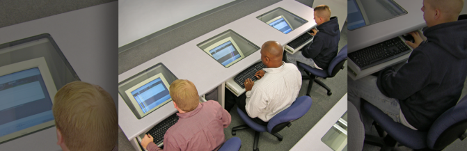Three participants in front of computers filling out online training evaluations.