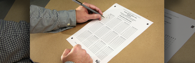 A close up view of a participant's hand writing on an evaluation answer sheet.