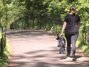 A woman walking down a wooded path.